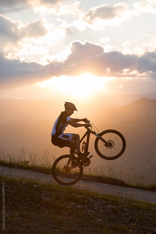 Young man doing tricks with bike at sunset by RG&B Images for Stocksy United