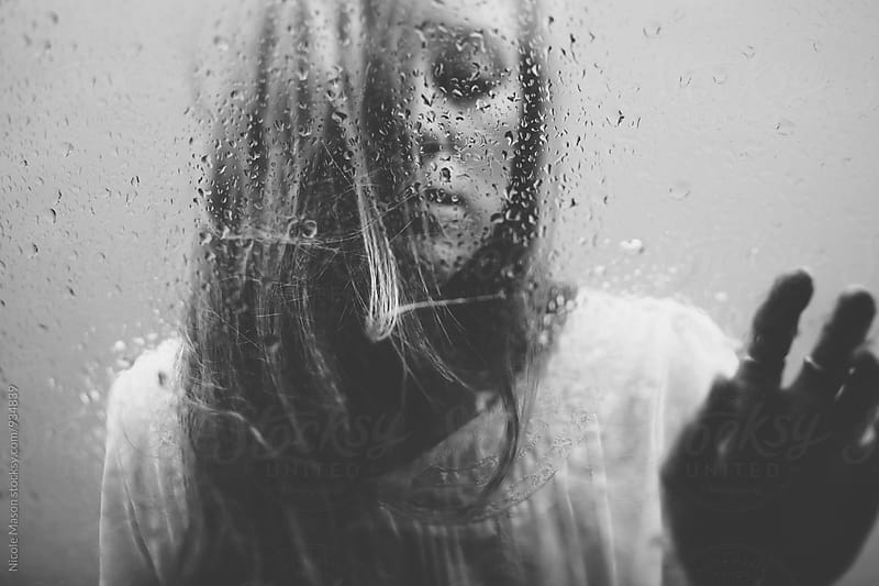 young blonde woman standing behind glass with rain drops by Nicole Mason for Stocksy United