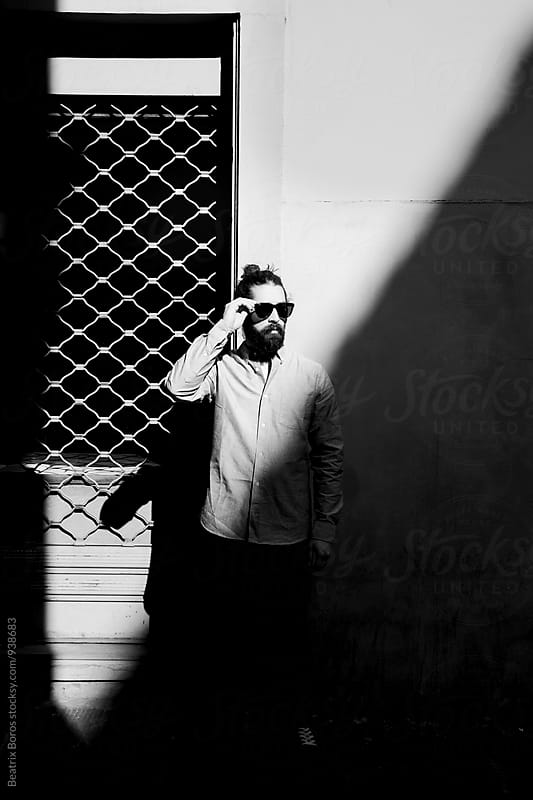 Man putting his sunglasses on in the Sun next to a closed shop by Beatrix Boros for Stocksy United