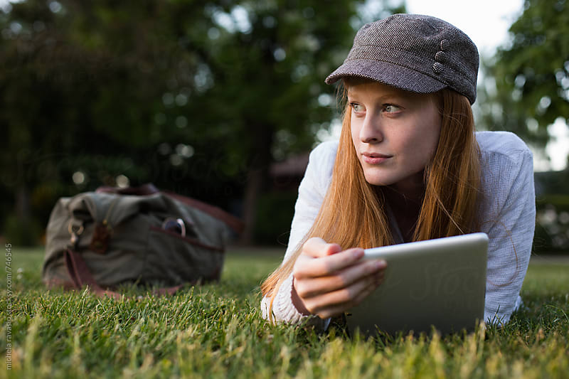 Young woman lying on the grass holding her digital tablet by michela ravasio for Stocksy United