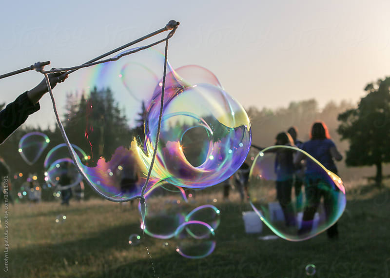 Huge shimmering soap bubble made with sticks and rope by Carolyn Lagattuta for Stocksy United