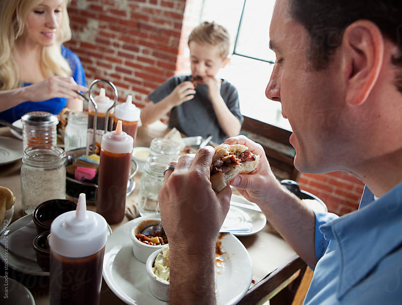 Barbeque: Father Eating Pulled Pork Sandwich by Sean Locke for Stocksy United