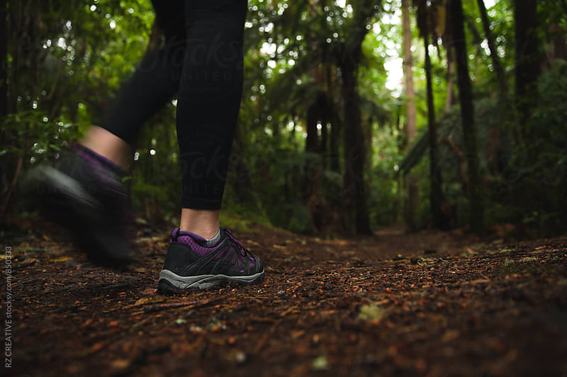 Woman wearing a rain jacket walking a trail in the forest. by Robert Zaleski for Stocksy United