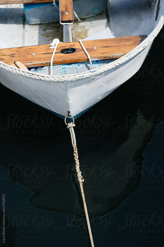 Rowboat floats in the water, tied to a dock by Cara Dolan for Stocksy United