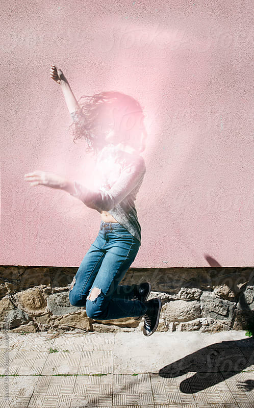 Young woman jumping in the air, her face is covered by light reflection by Beatrix Boros for Stocksy United