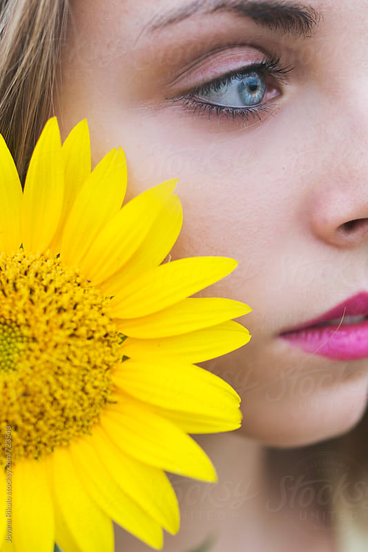 Young woman and sunflower close up by Jovana Rikalo for Stocksy United