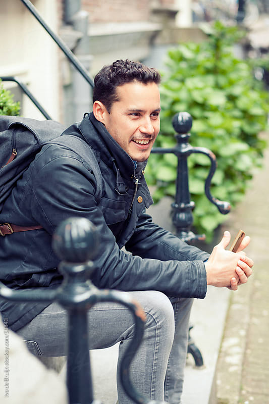 Young man of mixed race with a backpack sitting on a doorstep with his phone in his hands  by Ivo de Bruijn for Stocksy United