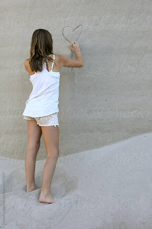 Girl carving a heart into a sand wall by Carolyn Lagattuta for Stocksy United