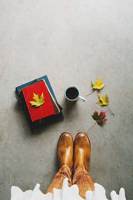 woman with boots stands next to books, coffee, and autumn leaves by Kelly Knox for Stocksy United
