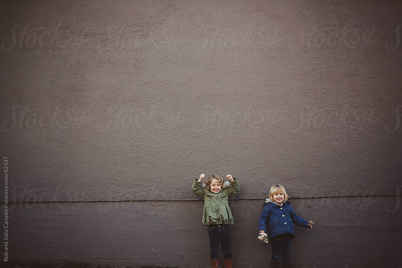 Cute, young girls having fun downtown in front of brown wall by Rob and Julia Campbell for Stocksy United
