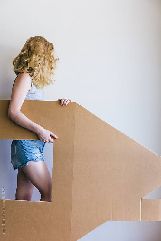Young woman carrying a cardboard cut out of a house by Jacqui Miller for Stocksy United