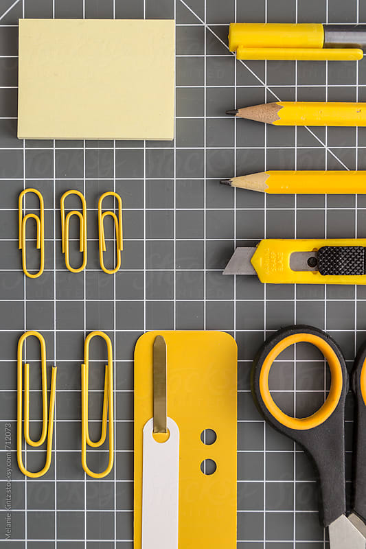 Yellow office utensils on a grey crafting mat by Melanie Kintz for Stocksy United