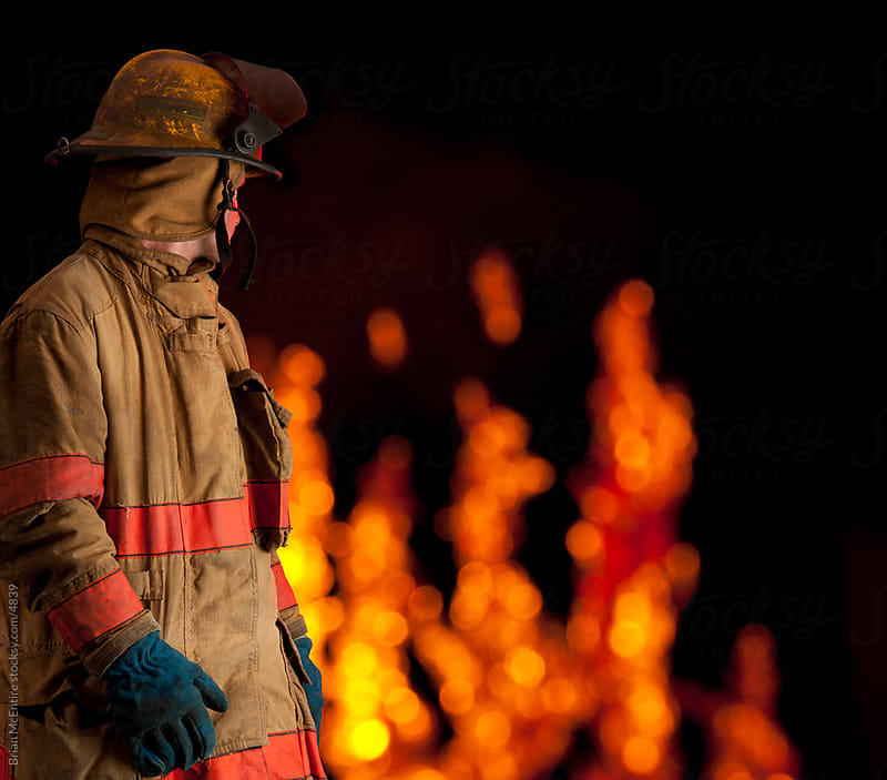 Fireman looks back at flaming building by Brian McEntire for Stocksy United