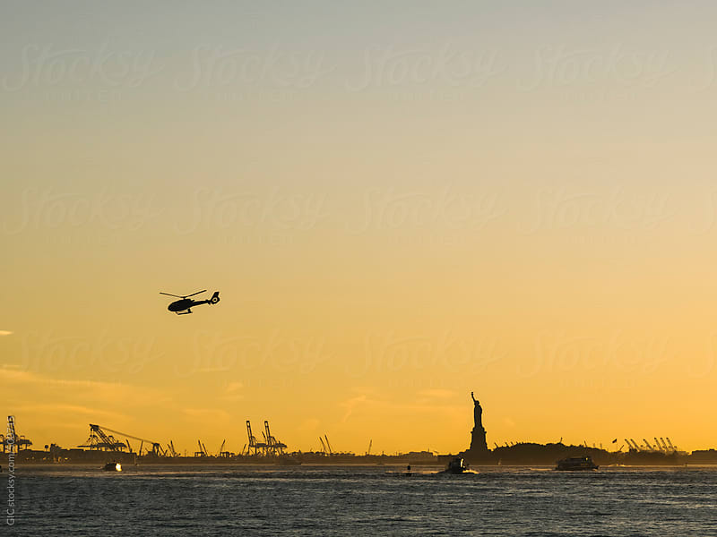 Helicopter and boats against Statue of Liberty in NY by GIC for Stocksy United