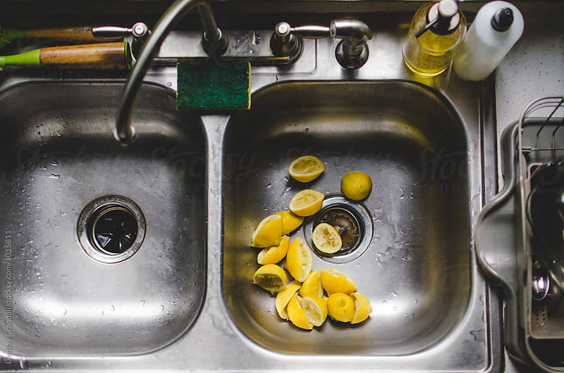 Squeezed lemons in the kitchen sink by Lindsay Crandall for Stocksy United