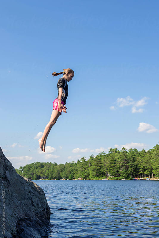 Girl does a pencil dive off a rock into the lake by Cara Dolan for Stocksy United
