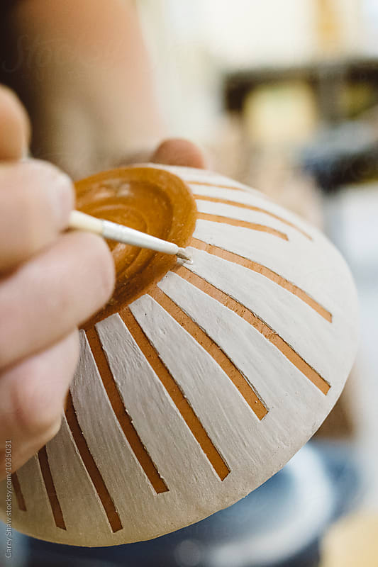 Glaze being applied to clay bowl by Carey Shaw for Stocksy United