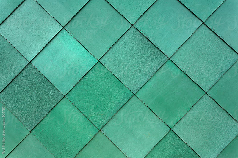 Square green cladding fastened to the exterior of a building to form a pattern by Paul Phillips for Stocksy United