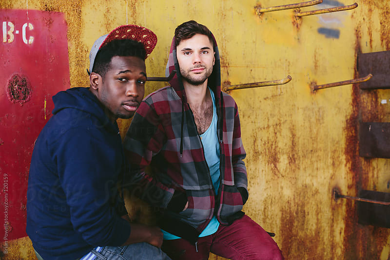 two urban friends looking at camera by Brian Powell for Stocksy United
