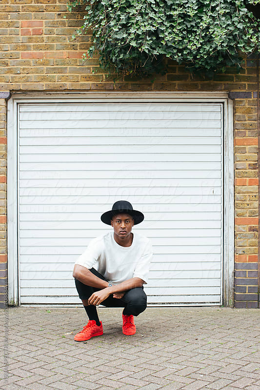 London Street Style - Outdoor Portrait of Cool Young Black Man Crouching in Front of White Garage Door by Julien L. Balmer for Stocksy United