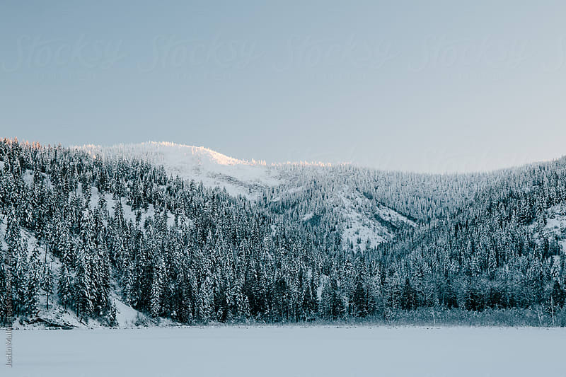 The first sunlight on a snow covered peak overlooking a frozen lake by Justin Mullet for Stocksy United