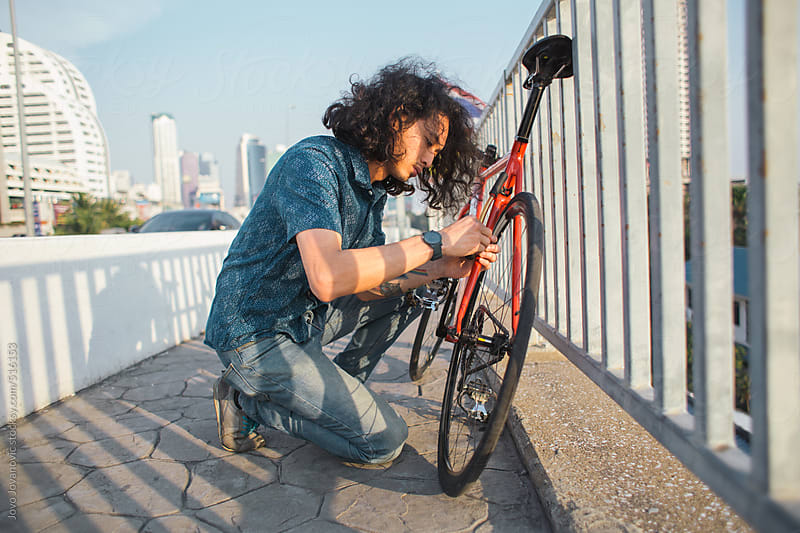 Asian man fixing his bicycle by Jovo Jovanovic for Stocksy United