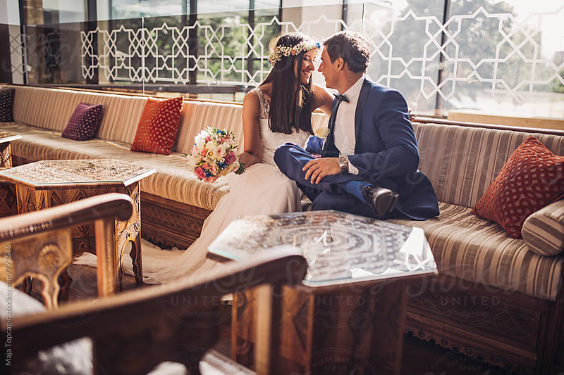 Bride and groom laughing in an oriental coffee shop by Maja Topcagic for Stocksy United