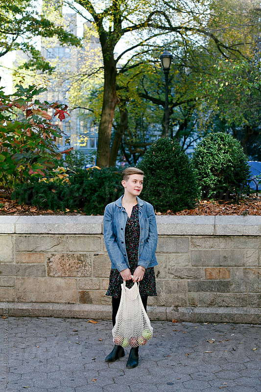 Young woman stands with mesh bag of apples by Jennifer Brister for Stocksy United