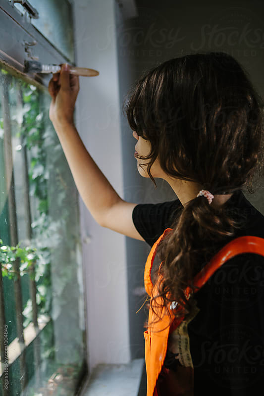 Young woman painting a window by kkgas for Stocksy United