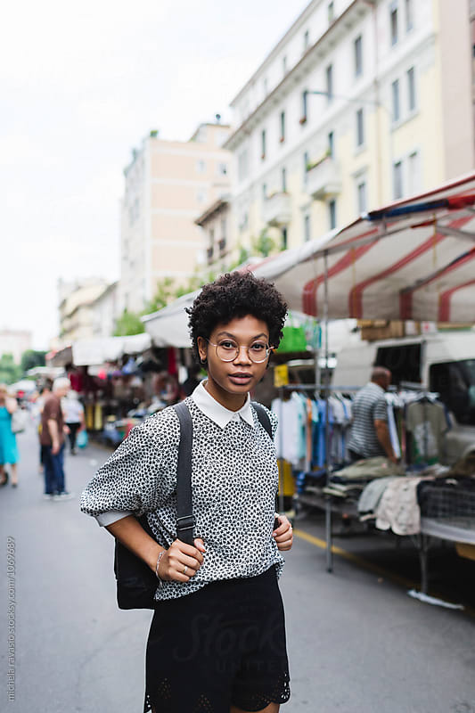 Portrait of beautiful woman with backpack at the market place by michela ravasio for Stocksy United