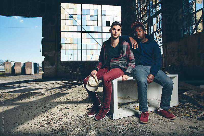two guys sitting in abandoned warehouse by Brian Powell for Stocksy United