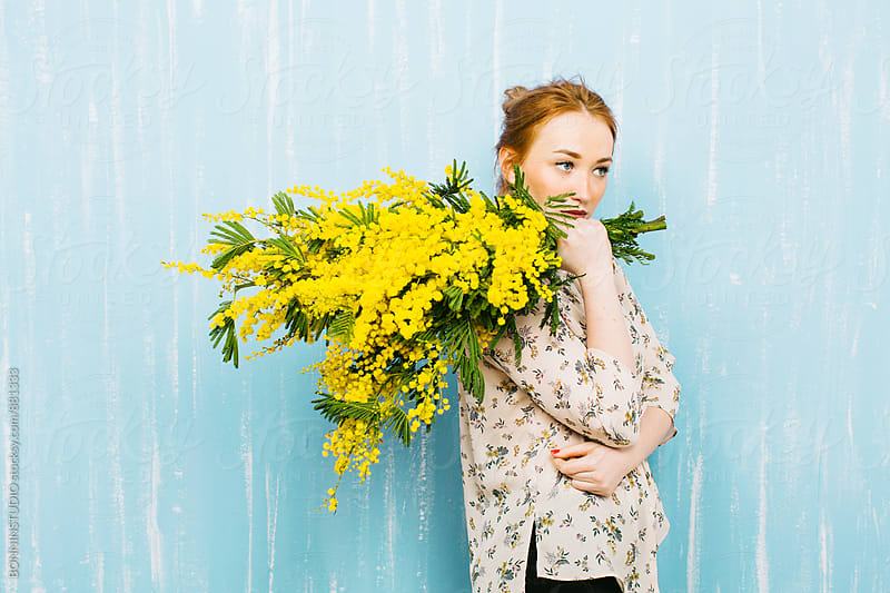 Side view of a young ginger woman holding a bouquet of yellow flowers. by BONNINSTUDIO for Stocksy United