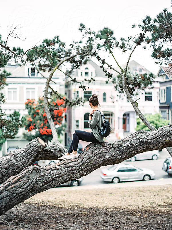Woman sitting on tree in San Francisco by Daniel Kim Photography for Stocksy United