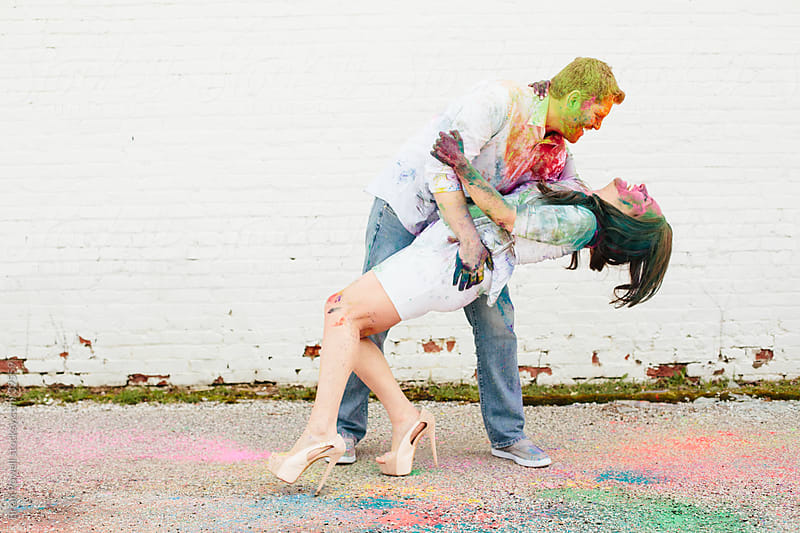 engaged couple covered in painted powder by Brian Powell for Stocksy United
