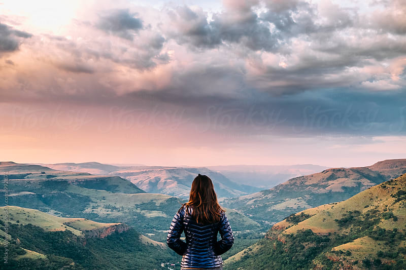 Hiker overlooking a scenic mountainous valley at sunset by Micky Wiswedel for Stocksy United
