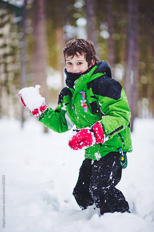 Boy about to throw a snowball by Angela Lumsden for Stocksy United