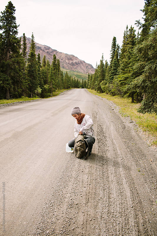 Young Man Rummaging Through His Backpack On A Gravel Road In Denali National Park by Luke Mattson for Stocksy United