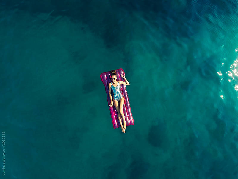 Overhead View of a Woman on a Pink Sea Mattress by Lumina for Stocksy United