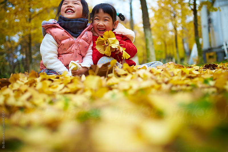 two lovely asian girl having fun in the autumn woods by Bo Bo for Stocksy United