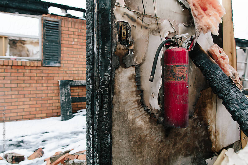house fire with unused fire extinguisher by Brian Powell for Stocksy United