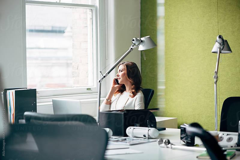 Ambitious Businesswoman talking on technology smart phone call device at work startup by Aila Images for Stocksy United