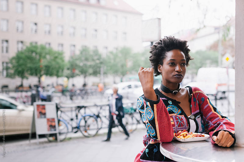 Woman eating a Currywurst by VegterFoto for Stocksy United