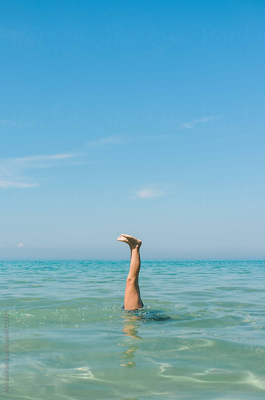 Swimmer doing a handstand underwater. by Melissa Ross for Stocksy United