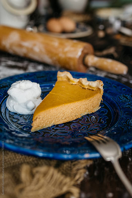 Pumpkin pie slice on a blue plate by Gabriel (Gabi) Bucataru for Stocksy United
