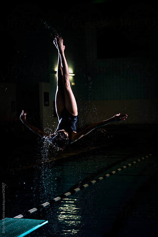 Female Diver Flipping off Diving Board, Water Spray Featured by Brian McEntire for Stocksy United