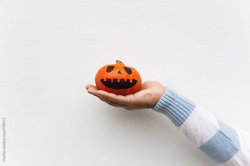 Male hands holding Halloween pumpkin in front of a white background by Marija Mandic for Stocksy United