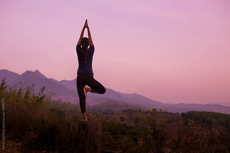 Woman practising yoga at sunrise in the mountains by Søren Egeberg Photography for Stocksy United