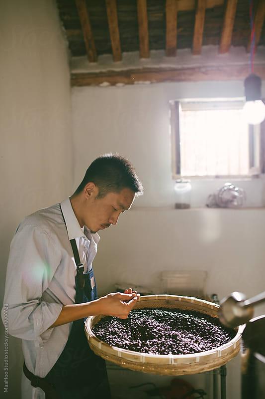 Man working at coffee roasting workshop by Maa Hoo for Stocksy United