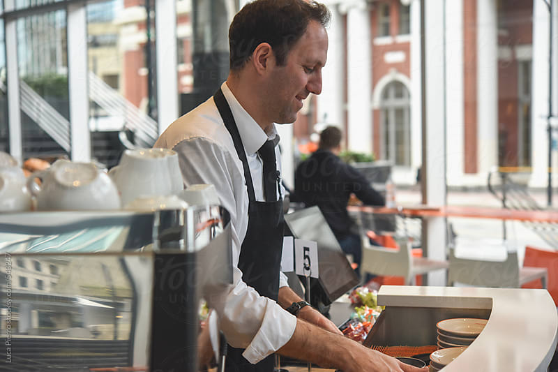 Bartender working in a coffee bar by Luca Pierro for Stocksy United