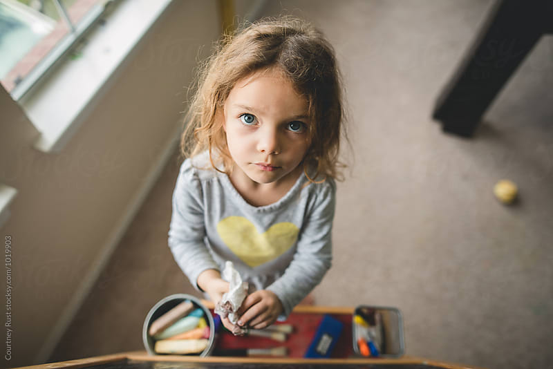 Little girl looking up while cleaning her board  by Courtney Rust for Stocksy United